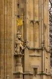 Ett lejon står vakten för den kungliga ingången nedanför det Victoria tornet på den brittiska parlamentbyggnaden i London, Englan fotografering för bildbyråer