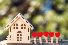 Ett leksakhus med ett staket av hjärtor Ett symbol av ett hus var lo Arkivbild
