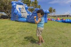 Ett litet barn gör hans lyckliga dans, medan hålla ögonen på ett dunshus att blåsa upp royaltyfri bild