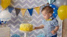 Ett litet barn sätter ett finger inom en födelsedagkaka stock video