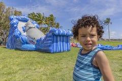Ett litet barn ser kameran med en förvirrad blick, medan dunshuset blåser upp royaltyfria bilder