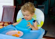 Ett litet barn som tycker om en tropisk frukost Arkivfoton