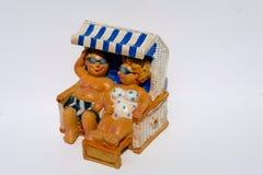 Ett litet dvärg- par på semester ligger kopplade av i en strandstol som isoleras på en vit bakgrund fotografering för bildbyråer