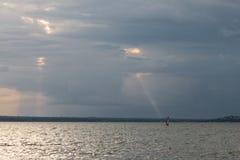 Ett litet, färgrikt vindsurfar på en sjö, under en molnig himmel med Arkivfoto