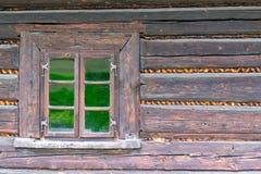 Ett litet f?nster i v?ggen av ett gammalt tr?hus arkivfoton