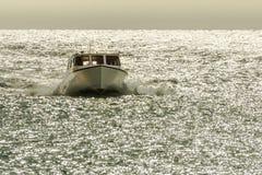 Ett litet fartyg rusar till och med det glittra havvattnet Royaltyfria Bilder