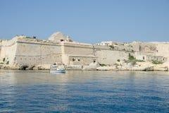 Ett litet fartyg seglar förbi väggarna av den forntida staden Arkivfoto