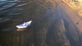 Ett litet fartyg som göras av papper och att svänga på vågorna nära stranden stock video