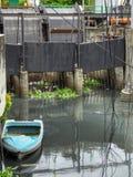 Ett litet fartyg som svävar i förorenat vatten i Bangkok royaltyfria foton