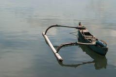 Ett litet gammalt träBalinesefartyg, blått målar på sidan, brutna platser, på som lämnas en stor motvikt, står på vattnet, wh Arkivbilder