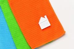 Ett litet hus ligger på en bunt av tre handdukar på en vit bakgrund royaltyfria bilder