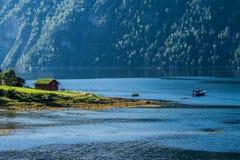 Ett litet hus med ett grönt tak nära floden och med ett litet fartyg som korsar den Arkivbilder