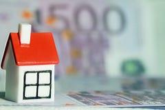 Ett litet hus på bakgrunden av pengar arkivfoton