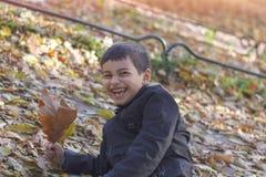 Ett litet lyckligt barn avverkar in i sidorna och skratten med glädje i höstträdgården arkivfoto