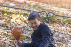 Ett litet lyckligt barn avverkar in i sidorna och skratten med gl?dje i h?sttr?dg?rden royaltyfria foton