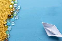 Ett litet pappers- fartyg seglar till den sandiga kusten Id?rikt minsta havs- och strandbegrepp seamless sommar f?r resaresthav o royaltyfria bilder
