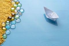 Ett litet pappers- fartyg seglar till den sandiga kusten Id?rikt minsta havs- och strandbegrepp seamless sommar f?r resaresthav L arkivbild