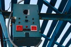 Ett litet transformatorkabinett fixas på en hög stång under en markis Arkivfoto