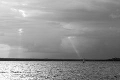 Ett litet vindsurfar på en sjö, under en molnig himmel med någon sol r Arkivbilder