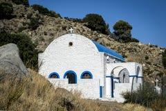 Ett litet vitt grekiskt kapell i de inlands- bergen Fotografering för Bildbyråer