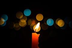 Ett ljus för stearinljusflamma på natten med bokeh på mörk bakgrund Arkivbild