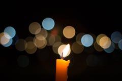 Ett ljus för stearinljusflamma på natten med bokeh på mörk bakgrund Royaltyfri Bild
