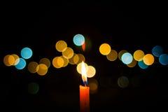Ett ljus för stearinljusflamma på natten med bokehbakgrund Arkivbilder