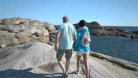 Ett lyckligt älska moget par tycker om en gå bland de kust- stenarna på kusten arkivfilmer
