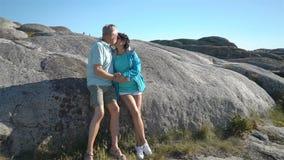 Ett lyckligt älska moget par tycker om en gå bland de kust- stenarna på kusten stock video