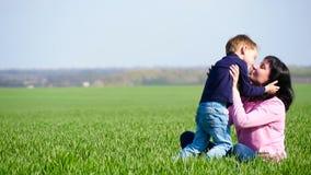 Ett lyckligt barn kör in i mammans armar, kramar henne och kysser henne lager videofilmer