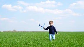 Ett lyckligt barn stöter ihop med en grön gräsmatta som rymmer en leksaknivå arkivfilmer