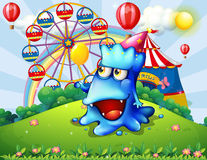 Ett lyckligt blått monster på bergstoppet med en karneval Royaltyfria Bilder