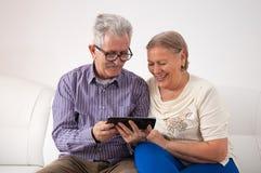 Ett lyckligt högt par genom att använda en digital minnestavla royaltyfri fotografi