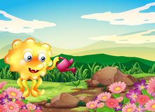 Ett lyckligt monster som bevattnar växterna på bergstoppet med blommor Arkivbilder
