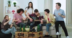 Ett lyckligt och attraktivt företag har en stor tid tillsammans i en rymlig vardagsrum dem som sjunger på en gitarr och dansa stock video