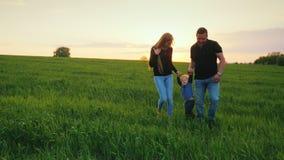 Ett lyckligt par av föräldrar med en liten son går över fältet in mot solnedgången lycklig barnfamilj