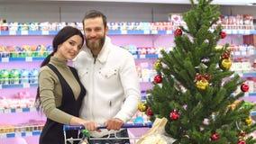Ett lyckligt par köper livsmedel för jul på livsmedelsbutiken långsam rörelse stock video