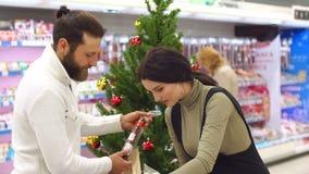 Ett lyckligt par köper livsmedel för jul på livsmedelsbutiken långsam rörelse arkivfilmer