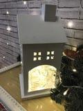 Ett lysande hus för liten vit leksak med ett rör står på en tabell mot bakgrunden av girlander, ljusa kulor och en tegelsten Arkivfoto