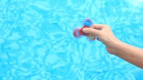 Ett mångfärgat, röd-guling-blått räcker spinnaren eller spinnaren som roterar på armen för person` s En kvinna som rotera en rast stock video