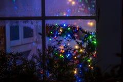 Ett magiskt sagolikt vinterfönster med leksaker och julgranljus fotografering för bildbyråer