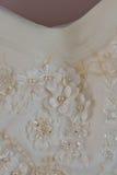 Ett makrofoto av en detaljerad vit bröllopsklänning med vita blommor och fejkar diamanter som stickas till klänningen Royaltyfria Foton