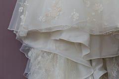 Ett makrofoto av en detaljerad vit bröllopsklänning med vita blommor och fejkar diamanter som stickas till klänningen Arkivfoto