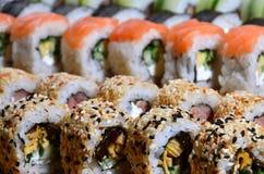 Ett makroskott av en sushiuppsättning av många rullar lokaliseras på en träskärbräda på en tabell i köket av en sushistång En tra Royaltyfria Bilder