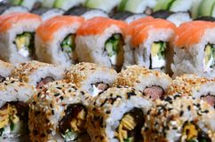 Ett makroskott av en sushiuppsättning av många rullar lokaliseras på en träskärbräda på en tabell i köket av en sushistång En tra Royaltyfri Bild