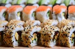 Ett makroskott av en sushiuppsättning av många rullar lokaliseras på en träskärbräda på en tabell i köket av en sushistång En tra Royaltyfria Foton