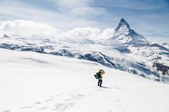 Ett mananseende på snön som ser bakgrunden av Matterhorn Arkivfoton