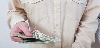 Ett mananseende som bär den ljusa kulöra officiella skjortan, rymmer i hans amerikanska dollar för handen royaltyfri fotografi