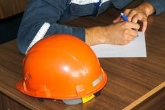 Ett manarbete som en tekniker med en hjälm för orange guling på tabellen studerar som skriver i en anteckningsbok på en industria royaltyfria foton