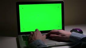 Ett manbruk en bärbar dator på hans skrivbord stock video